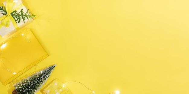 Рождество новая нормальная концепция рабочего пространства в желтом цвете. рамка блокнота-органайзера на 2021 год, маленькая новогодняя елка, подарочная коробка своими руками, защитная маска для лица, рождественские фонари. планирование. вид сверху, плоская планировка. скопируйте пространство.