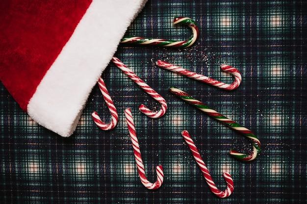 Рождество новый год фон клетки, плоский стиль с видом сверху с рождественскими украшениями, шляпой и рождественской тростью, место для вашего текста