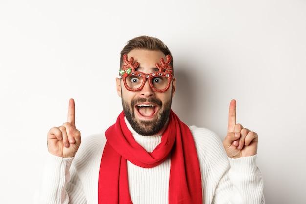 クリスマス、新年、お祝いのコンセプト。パーティーグラスと赤いスカーフでハンサムなひげを生やした男のクローズアップ、冬休みを祝い、コピースペースで指を指さします