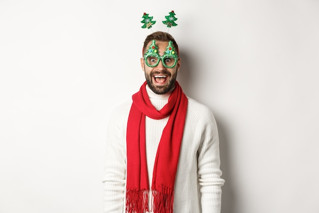 Рождество, новый год и концепция празднования. красивый бородатый мужчина выглядит удивленным, в партийных очках и аксессуарах, на белом фоне