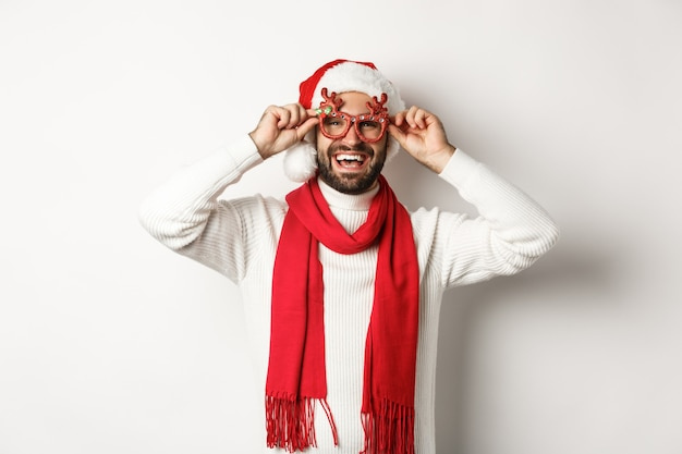 크리스마스, 새 해 및 축 하 개념입니다. 행복 한 남자 웃 고, 산타 모자와 파티 안경을 쓰고 흰색 배경 위에 서