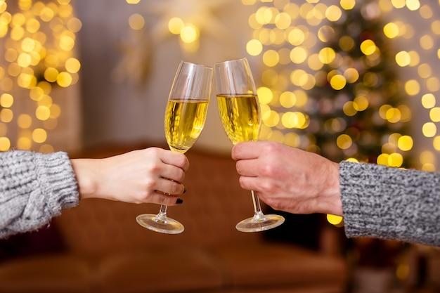 クリスマス、新年、愛のコンセプト-装飾されたリビングルームで男性と女性の手でシャンパングラスのクローズアップ