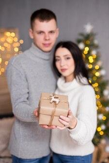 クリスマス新年と愛の概念の若いカップルの愛のギフトボックスを保持します。