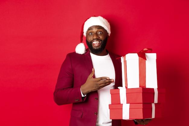 Рождество, новый год и концепция покупок. веселый черный человек секретный санта держит рождественские подарки и улыбается взволнованно, приносит подарки, стоя на красном фоне.