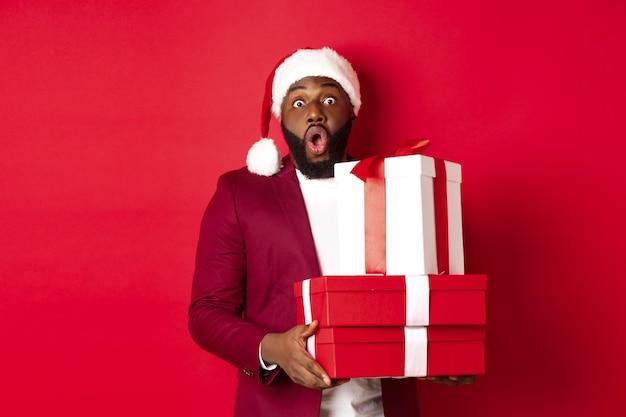 크리스마스, 새해 및 쇼핑 개념입니다. 쾌활한 흑인 남자 비밀 산타 크리스마스 선물을 들고 흥분 미소, 선물을 가져, 빨간색 배경에 서