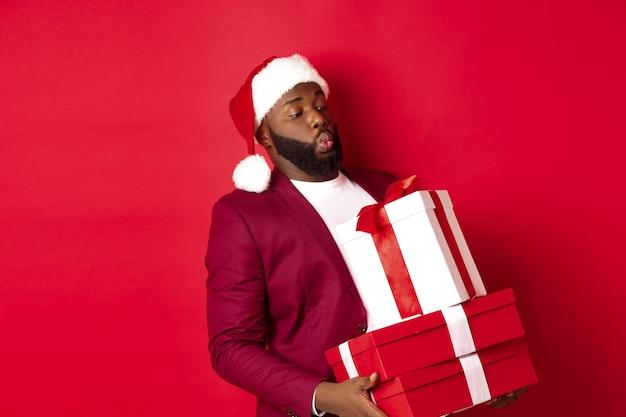 クリスマス、新年、ショッピングのコンセプト。サンタの帽子をかぶった面白いアフリカ系アメリカ人の男は、重いクリスマスプレゼントを運び、贈り物を持って、赤い背景の上に立っています