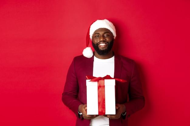 크리스마스, 새해 및 쇼핑 개념입니다. 크리스마스 선물을 들고 카메라를 보며 웃고 있는 수염난 아프리카계 미국인 남자, 빨간 배경에 산타 모자를 쓰고 서 있다