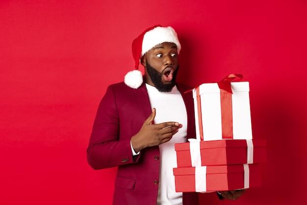 クリスマス、新年、ショッピングのコンセプト。クリスマスを見て驚いた黒人男性は、サンタの帽子をかぶって、赤い背景に贈り物を持って立って、驚きを提示します