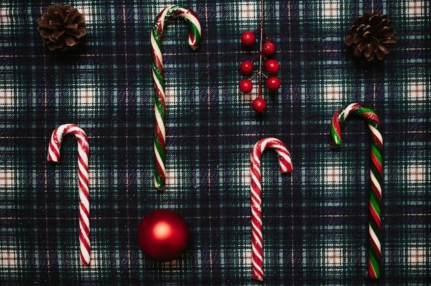 Рождественский новогодний фон, плоский стиль с видом сверху с рождественскими украшениями из конусов, шаров и рождественской трости, на в клетке, место для вашего текста.