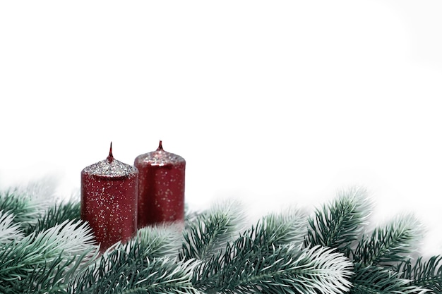 Christmas new year background for greeting card. christmas tree branches with snow effectred candles, on white background, copy space