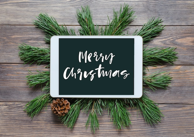 Christmas or new year background on a wooden background handwritten inscription on the gadget screen