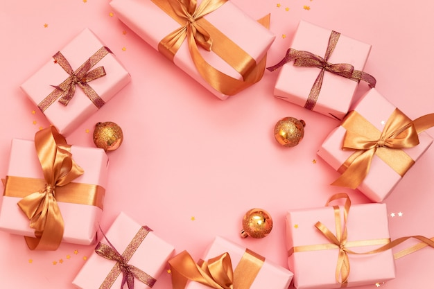 Christmas or new year banner frame with golden balls, paper pink gift boxes decorated with shiny gold ribbons on a pink .