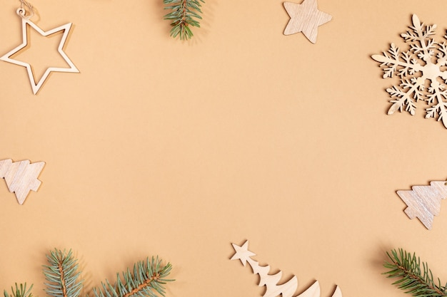 Christmas or new year beige background with frame of wooden festive decorations - xmas toys and fir tree twigs with copy space in center. top view. horizontal orientation.