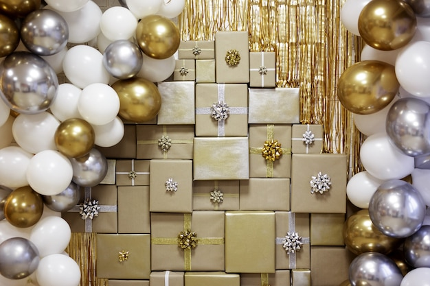 Christmas, new year or birthday background - decorated wall with golden and silver balloons and wrapped gift boxes