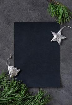 Рождество, новый год, черный стильный фон и бланк с веткой из ели и серебряной звездой. скопируйте пространство. вид сверху