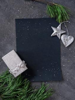 Рождество, новый год, черный стильный фон и бланк с веткой ели, подарок с украшениями из серебряных звезд. скопируйте пространство. вид сверху