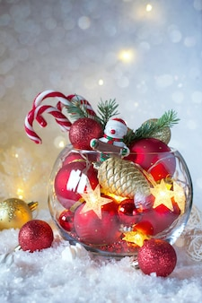 Christmas or new year bright decoration in glass vase with candy canes on snow