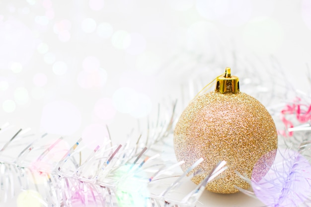 Christmas and new year card with gold ball and silver tinsel.