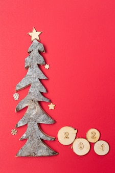 Christmas and new year card with wood numbers 2021 and christmas tree made of wood on red background.