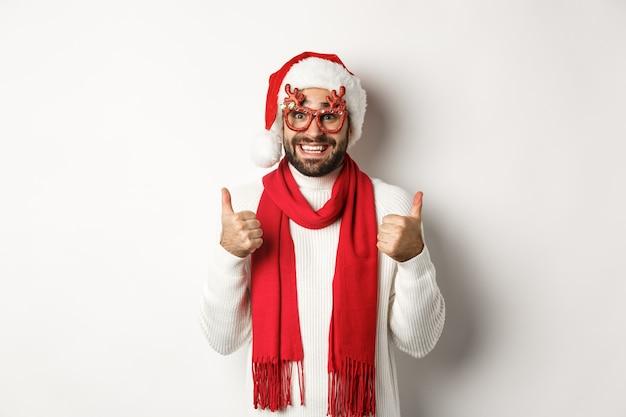 Natale, capodanno e concetto di celebrazione. uomo eccitato con cappello da babbo natale e occhiali da festa, che mostra i pollici in su in segno di approvazione, sorride soddisfatto, sfondo bianco