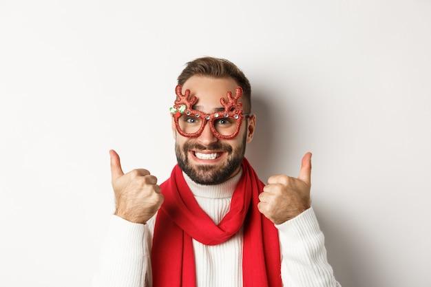 Natale, capodanno e concetto di celebrazione. uomo felice e soddisfatto con la barba, con gli occhiali da festa, che mostra i pollici in segno di approvazione o simili, in piedi su sfondo bianco
