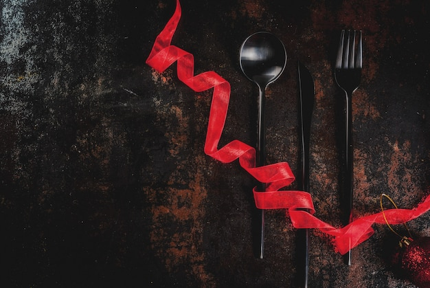 Christmas, new year celebration concept, set of silverware on a dark rusty scene,decorated with red ribbon and christmas tree ball