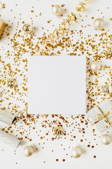 クリスマス/新年の作曲。クリスマスつまらないもの、ギフトボックス、見掛け倒し、白い背景の上の金の装飾で作られたコピースペースと空白の花輪フレーム。フラットレイ、トップビューのお祝いの休日のモックアップ。