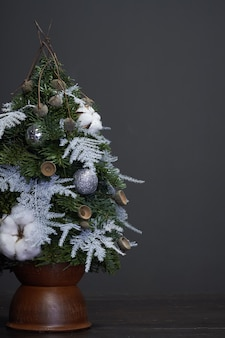 Christmas and new year composition. christmas tree made of fir branches and decorated by natural materials and balls in a clay pot