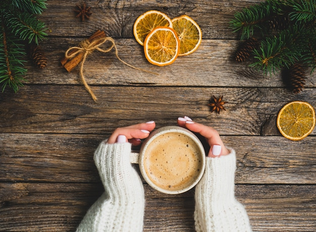 Christmas or new year composition of female hands, hot winter drink, spruce branches, orange chips, cinnamon, cones, anise, cozy sweater on rustic wooden background