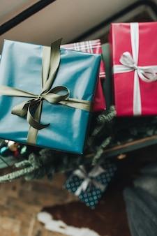 크리스마스 새 해 구성. 녹색과 회색 리본이 달린 파란색과 빨간색 종이로 포장하는 축제 수제 선물 상자