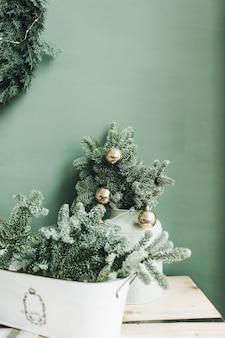 クリスマスの新年の構成。淡い緑の壁にモミの枝と金のボールとお祝いのテーブル
