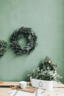 Christmas new year composition. festive table with fir branches, cup of coffee and christmas wreath against pale green wall.