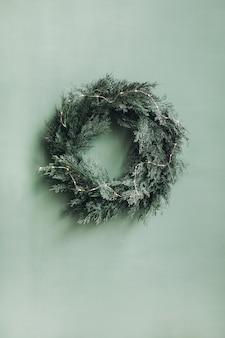 クリスマスの新年の構成。淡い緑の壁にクリスマスツリー、モミの枝、花輪で作られたお祝いの花輪