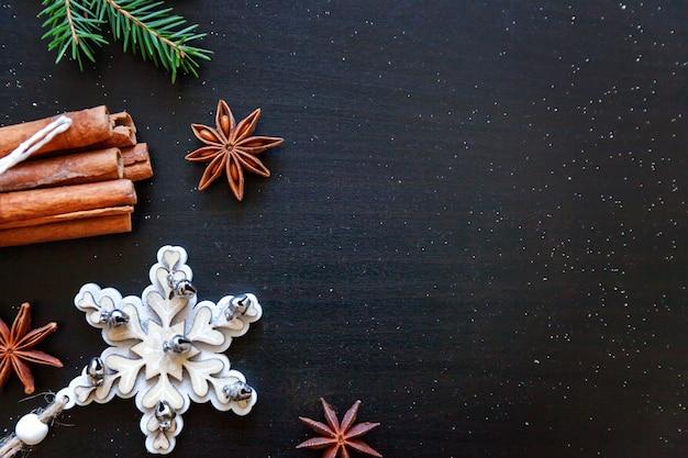 ダークブラックの背景に冬のオブジェクトモミの枝飾りシナモンで作られたクリスマス新年作曲フレーム