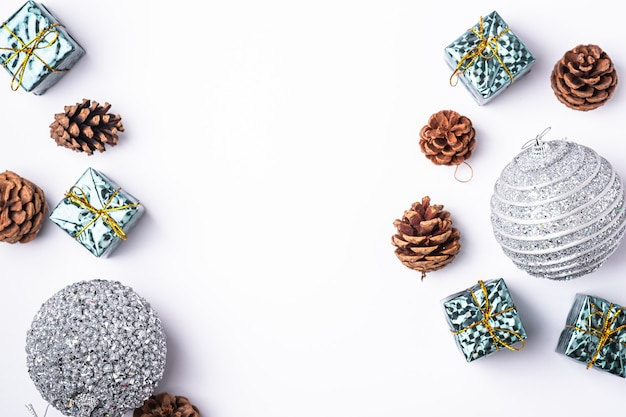 Christmas new year composition. gifts, fir tree cones, silver ball decorations on white background. winter holidays concept. flat lay, top view, copy space