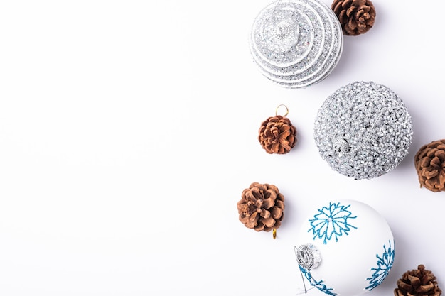 Christmas new year composition. gifts, fir tree cones, silver ball decorations on white background. winter holidays concept. top view copy space