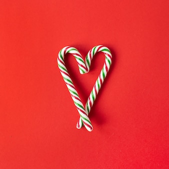 Christmas new year composition. heart symbol made of candy cane sticks on red