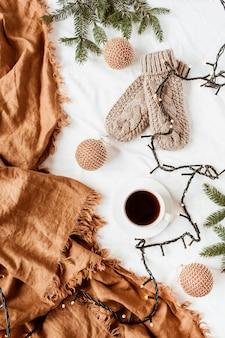 Рождественский новогодний состав. вязаные варежки, кофейная чашка, гирлянда, еловые ветки, рождественские безделушки, имбирный плед на белом одеяле