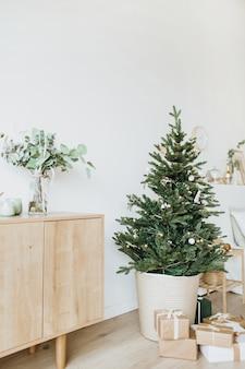 クリスマスの新年の構成。おもちゃ、ギフト、ボールで飾られたお祝いのモミの木のあるリビングルーム。