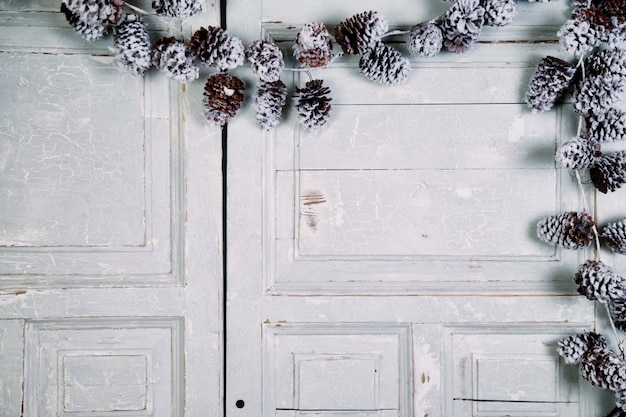 Christmas and new year composition - pine cones on wooden white doors background. old textured background with spruce and pine cones with meeting xmas and happy new year. copy space for site
