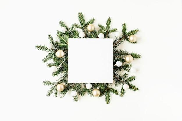 クリスマスの新年の構成。空白のコピースペース、モミの枝、白のクリスマスボールと正方形のモックアップフレーム