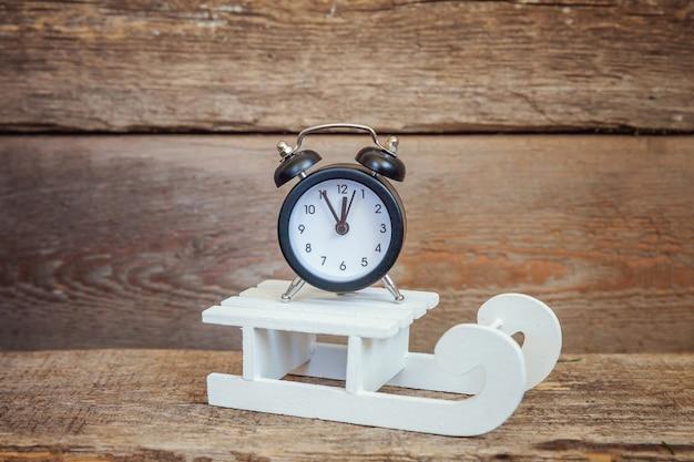 クリスマス新年作曲冬オブジェクト目覚まし時計と古いぼろぼろの素朴な木製の背景のそり