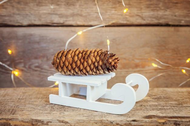 クリスマス新年作曲冬オブジェクトガーランドライト松ぼっくりと木製の背景にそり
