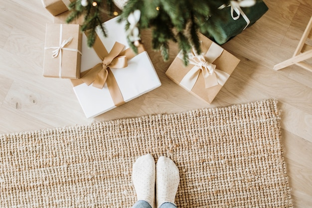 Christmas, new year composition with handmade gift boxes, fir-tree branches and women feet