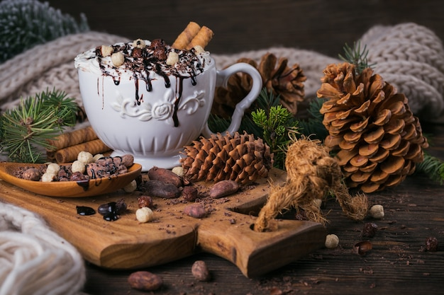 Christmas or new year composition with hot chocolate or cocoa drink with whipped cream served with chopped chocolate and cacao beans on rustic wooden plate.