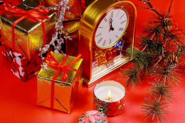Christmas or new year composition with red background candle. twelve o clock. new year s concept.
