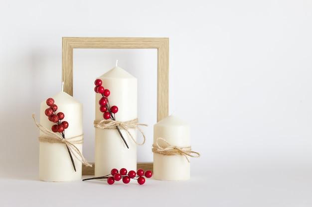 크리스마스, 새해 구성에는 흰색 촛불 3개, 붉은 열매, 흰색 바탕에 나무 틀이 있습니다.