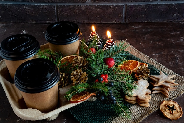 Christmas and new year compositions on a brown background cones spruce gingerbread coffee