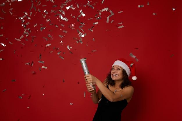 크리스마스, 새 해 개념입니다. 세련된 젊은 혼혈 여성은 고급스러운 벨벳 이브닝 드레스와 산타 모자를 쓰고 색종이 조각을 던지고 빨간색 배경에 플라잉 스팽글로 포즈를 취했습니다. 복사 공간