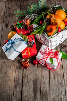Christmas and new year concept. fresh tangerines with green leaves in a white basket, christmas decoration and gift boxes, on old rustic wooden table,  top view
